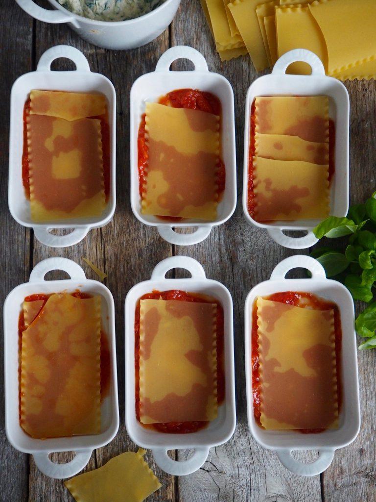 Fordel en tredjedel av tomatsausen i bunnen av formene.
