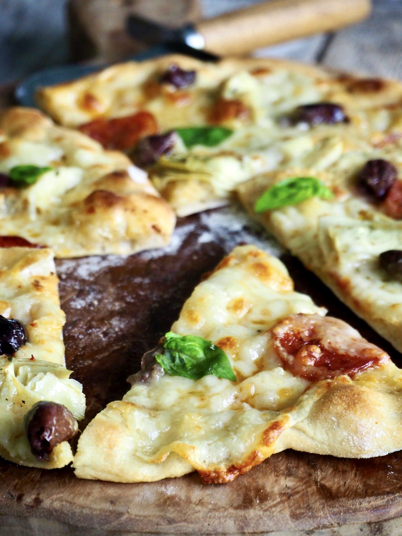 Hvit pizza med spekepølse, artisjokker og oliven